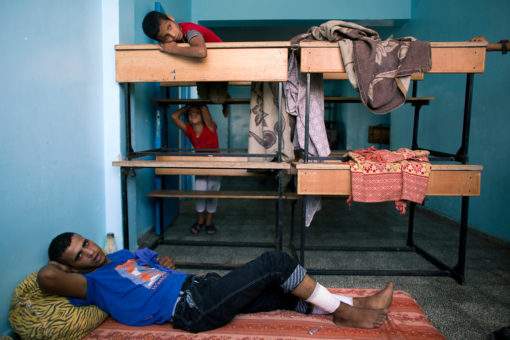 . In this photo made on Friday Aug. 8, 2014, Mohammed Abu Habsa, 21, rests in a U.N. school in Rafah, Gaza Strip. Mohammed was wounded on August 3, 2014, in shelling outside the school, where he and his family took refuge. Around 250,000 of Gazaís 1.8 million residents have been displaced, while some 65,000 lost their home in the fighting, according to U.N. figures. (AP Photo/Dusan Vranic)