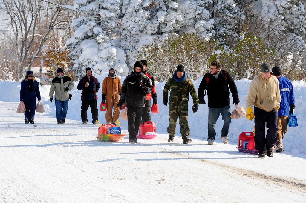 . Neighbors band together for a supply run on groceries and gas to help them dig out after a massive snow fall in Lancaster, N.Y. Wednesday, Nov. 19, 2014. Another two to three feet of snow is expected in the area.  (AP Photo/Gary Wiepert)