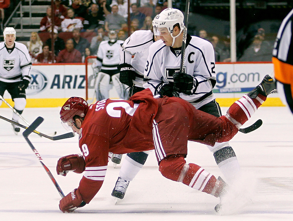 . Los Angeles Kings right winger Dustin Brownm, top, checks Phoenix Coyotes defenseman Michael Stone, bottom, to the ice in the first period of an NHL hockey game Tuesday, April 2, 2013, in Glendale, Ariz. (AP Photo/Paul Connors)