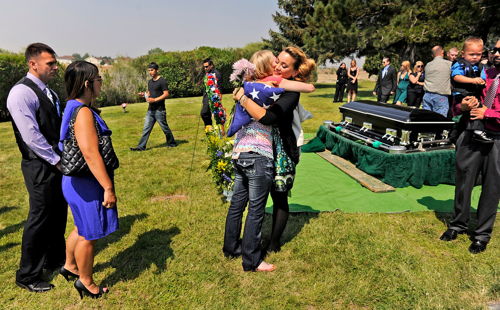 . Chantel Blunk, right of center, hugs Gina Dawsen after the service for her husband, Jonathan Blunk, Friday, August 03, 2012, at Mountain View Cemetery in Reno, Nevada.