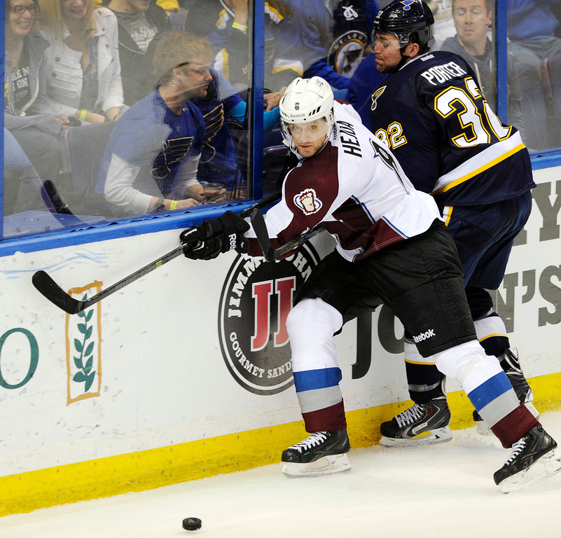 . St. Louis Blues\' Chris Porter (32) and Colorado Avalanche\'s Jan Hejda, of Czech Republic, battle for the puck during the third period of an NHL hockey game, Saturday, April 5, 2014, in St. Louis. (AP Photo/Bill Boyce)