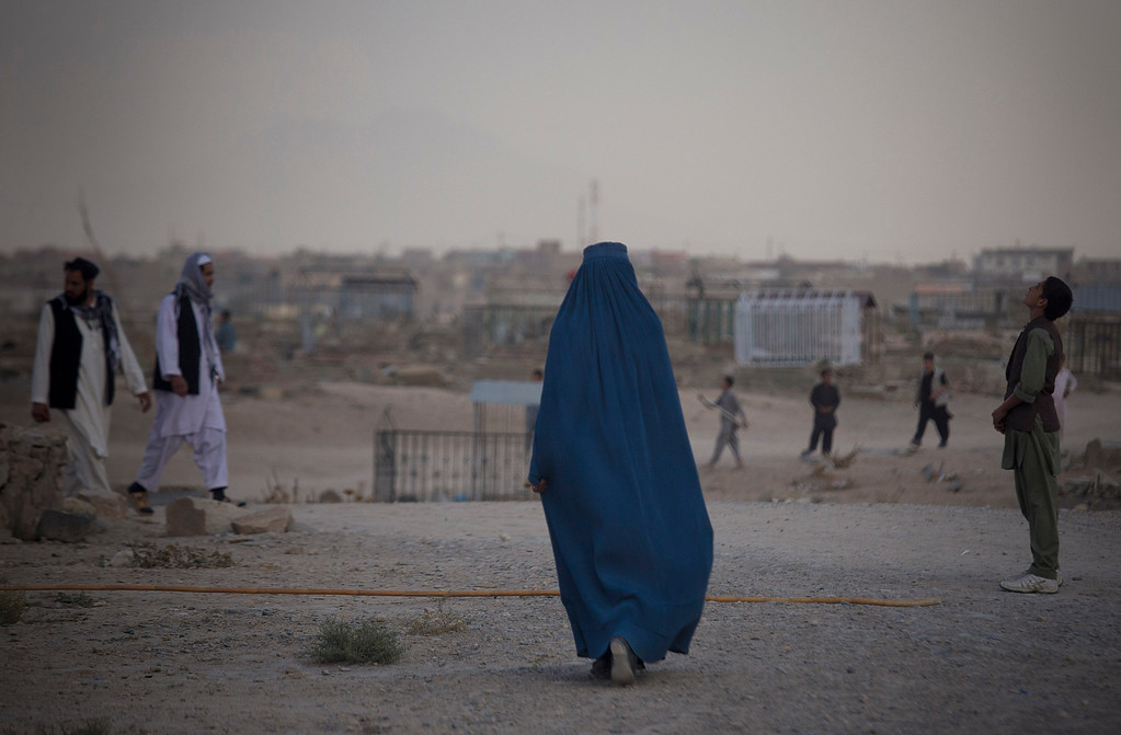. An Afghan woman in a burqa crosses a cemetery where children are flying their kites on a hill overlooking Kabul, Afghanistan, Wednesday, Oct. 16, 2013. During the Eid al-Adha holidays, families often visit the graves of their relatives. (AP Photo/Anja Niedringhaus)