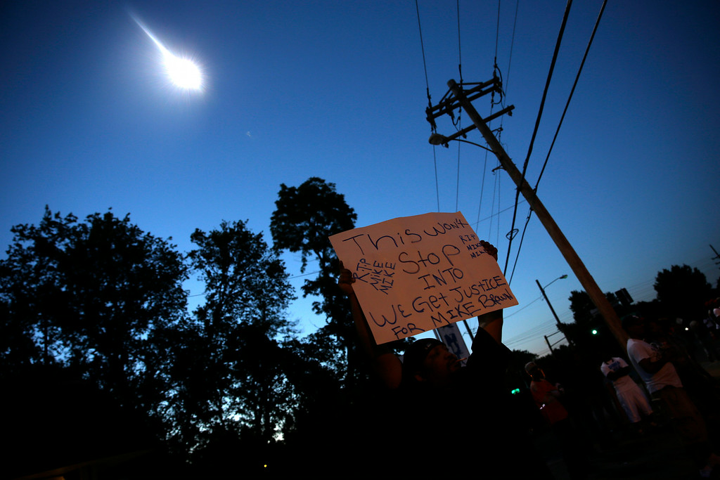 . A protester holds up a sign as a police helicopter circles overhead Wednesday, Aug. 13, 2014, in Ferguson, Mo. Protests in the St. Louis suburb rocked by racial unrest since a white police officer shot an unarmed black teenager to death turned violent Wednesday night, with some people lobbing Molotov cocktails and other objects at police who responded with smoke bombs and tear gas to disperse the crowd. (AP Photo/Jeff Roberson)