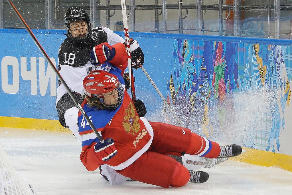 . Alexandra Kapustina of Russia crashes in front of Tomoko Sakagami of Japan during the 2014 Winter Olympics women\'s ice hockey game at Shayba Arena Sunday, Feb. 16, 2014, in Sochi, Russia. (AP Photo/Matt Slocum)