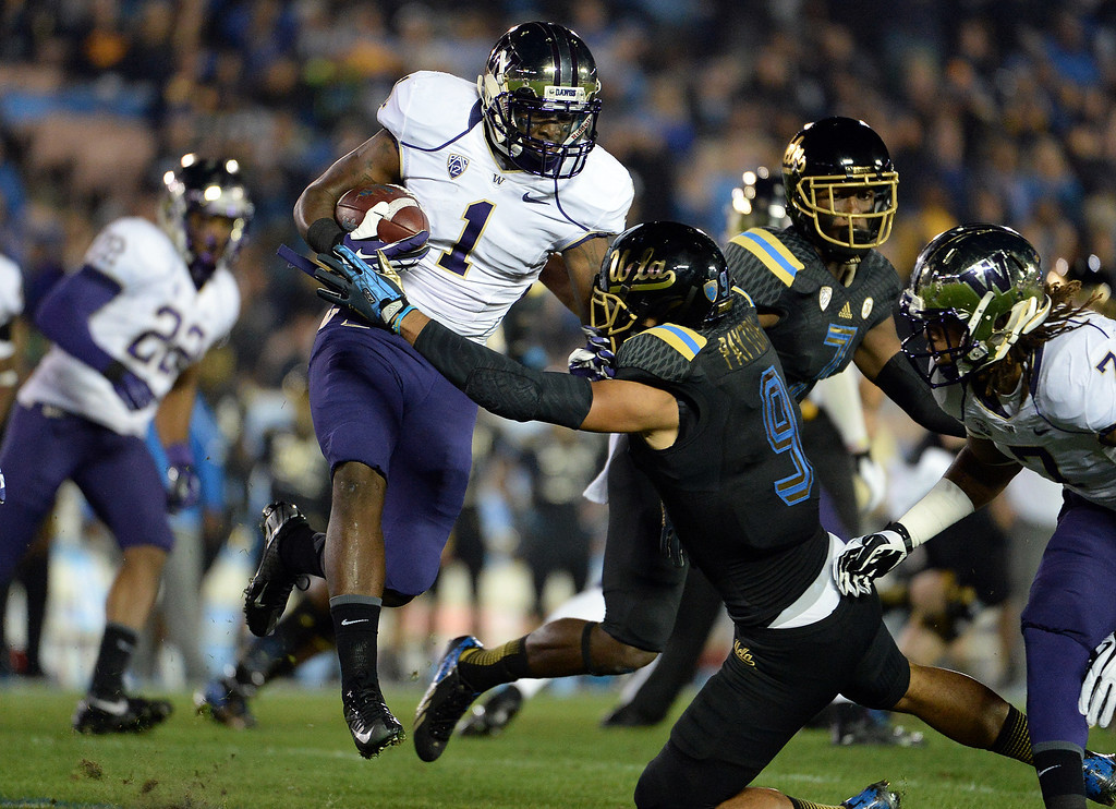 . Washington Huskies\'s John Ross (1) runs for a first down against UCLA Bruins during the first half of their college football game in the Rose Bowl in Pasadena, Calif., on Friday, Nov. 15, 2013.  UCLA won 41-31.   (Keith Birmingham Pasadena Star-News)
