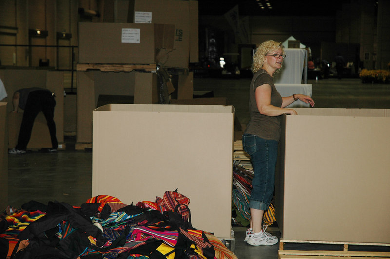 Vickie Davis, Team Leader for Volunteers, pauses for a moment to instruct over 50 volunteers who work in assemblyline fashion to load 40,000 backpacks with a Guidebook, Gatheirng Bible, and other inserts to be given to wach attendee of the 2006 ELCA Youth Gathering.