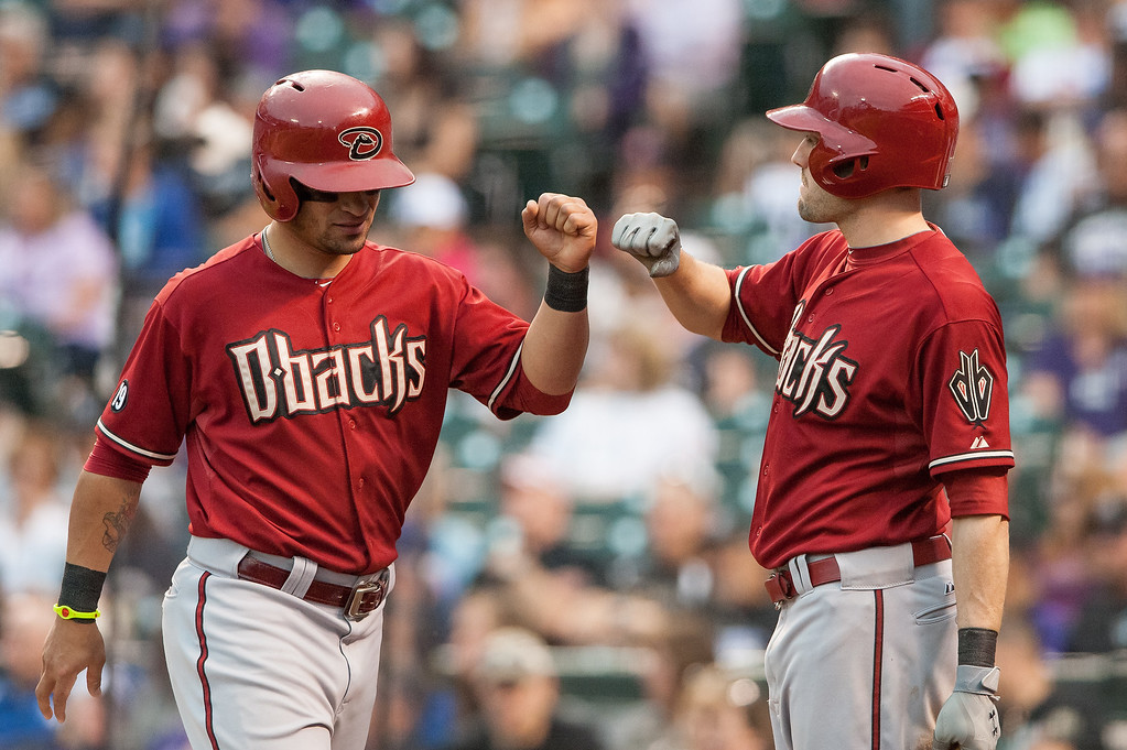 . Gerardo Parra #8 of the Arizona Diamondbacks celebrates a ninth inning run with A.J. Pollock #11 against the Colorado Rockies at Coors Field on September 22, 2013 in Denver, Colorado.  (Photo by Dustin Bradford/Getty Images)