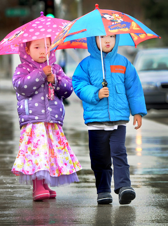 . Elliana Wang, 4, left, with her twin brother Marcus Wang of Pasadena, stay dry while carrying their Disneyland Mickey Mouse umbrellas on Colorado Boulevard in Pasadena Tuesday, February 19, 2013. (SGVN/Photo by Walt Mancini/SXCity)