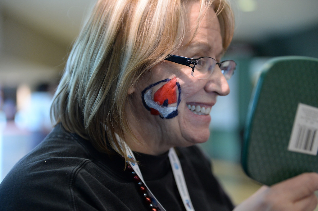 . Sherry Schulz checks out her Avalanche face paint before the game.   (Photo by Karl Gehring/The Denver Post)