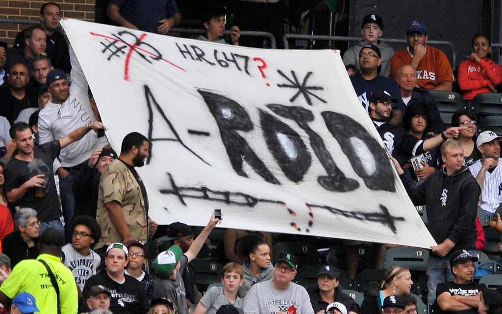 . Fans holds a sign made for New York Yankees\' Alex Rodriguez during the first inning of a baseball game between Yankees and the Chicago White Sox in Chicago, Monday, Aug. 5, 2013. Rodriguez was suspended through 2014 when Major League Baseball disciplined 13 players in a drug case, the most sweeping punishment since the Black Sox scandal nearly a century ago. (AP Photo/Paul Beaty)