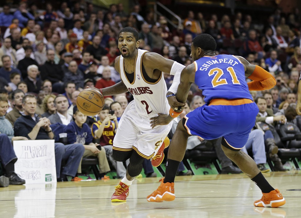 . Cleveland Cavaliers\' Kyrie Irving (2) drives on New York Knicks\' Iman Shumpert (21) in an NBA basketball game Tuesday, Dec. 10, 2013, in Cleveland. (AP Photo/Mark Duncan)