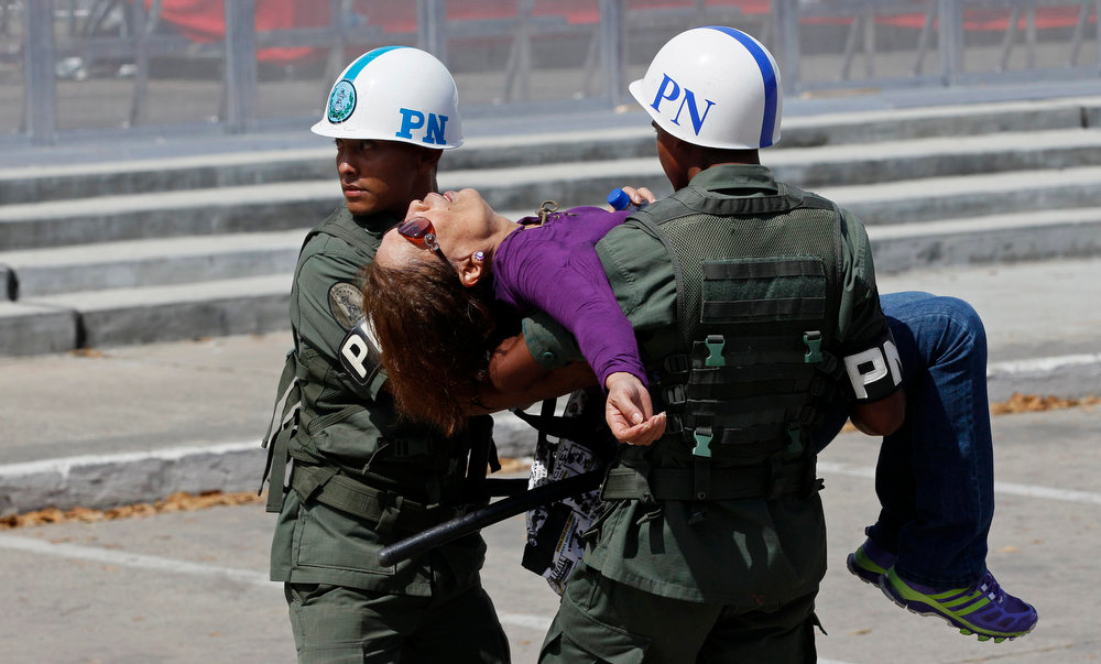 . Military police carry a woman who fainted while waiting in line to see the body of Venezuela\'s late President Hugo Chavez lying in state at the military academy in Caracas on Thursday, March 7, 2013. While Venezuela remains deeply divided over the country\'s future, the multitudes weeping and crossing themselves as they reached the president\'s coffin early Thursday were united in grief and admiration for a man many considered a father figure. (AP Photo/Rodrigo Abd)