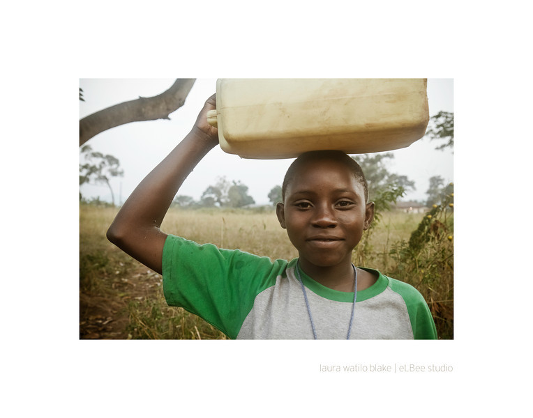 BALANCING ACT Maureen, a boarding school student, carries a full jerry can of water on her head.