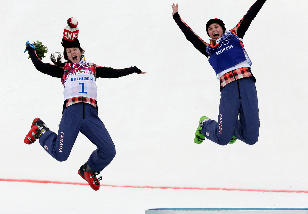 . Women\'s ski cross gold medalist Marielle Thompson of Canada, right, celebrates on the podium with silver medalist and compatriot Kelsey Serwa, left, at the Rosa Khutor Extreme Park, at the 2014 Winter Olympics, Friday, Feb. 21, 2014, in Krasnaya Polyana, Russia. (AP Photo/Andy Wong)