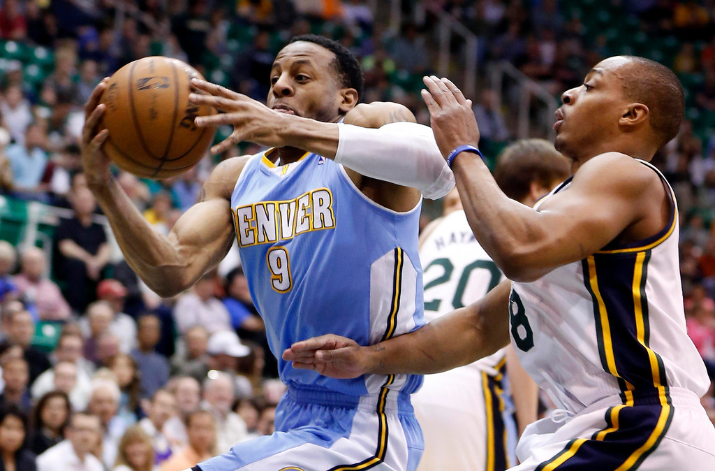 . Denver Nuggets guard Andre Iguodala (9) drives past Utah Jazz guard Randy Foye (8) during the first half of their NBA basketball game in Salt Lake City, Utah, April 3, 2013. REUTERS/Jim Urquhart