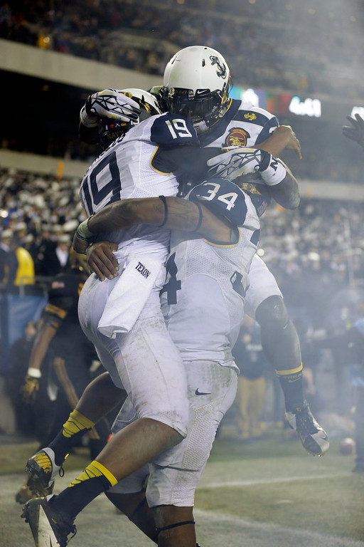 . Navy\'s Keenan Reynolds (19) celebrates a touchdown with Noah Copeland (34) and Gee Gee Greene, top, during the second half of an NCAA college football game against Army, Saturday, Dec. 8, 2012, in Philadelphia. Navy won 17-13. (AP Photo/Matt Rourke)