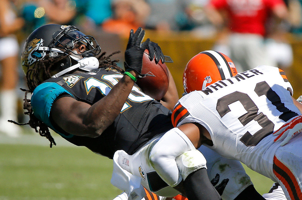 . Jacksonville Jaguars running back Denard Robinson, left, is brought down by Cleveland Browns strong safety Donte Whitner (31) after a run during the first half of an NFL football game in Jacksonville, Fla., Sunday, Oct. 19, 2014. (AP Photo/Stephen B. Morton)