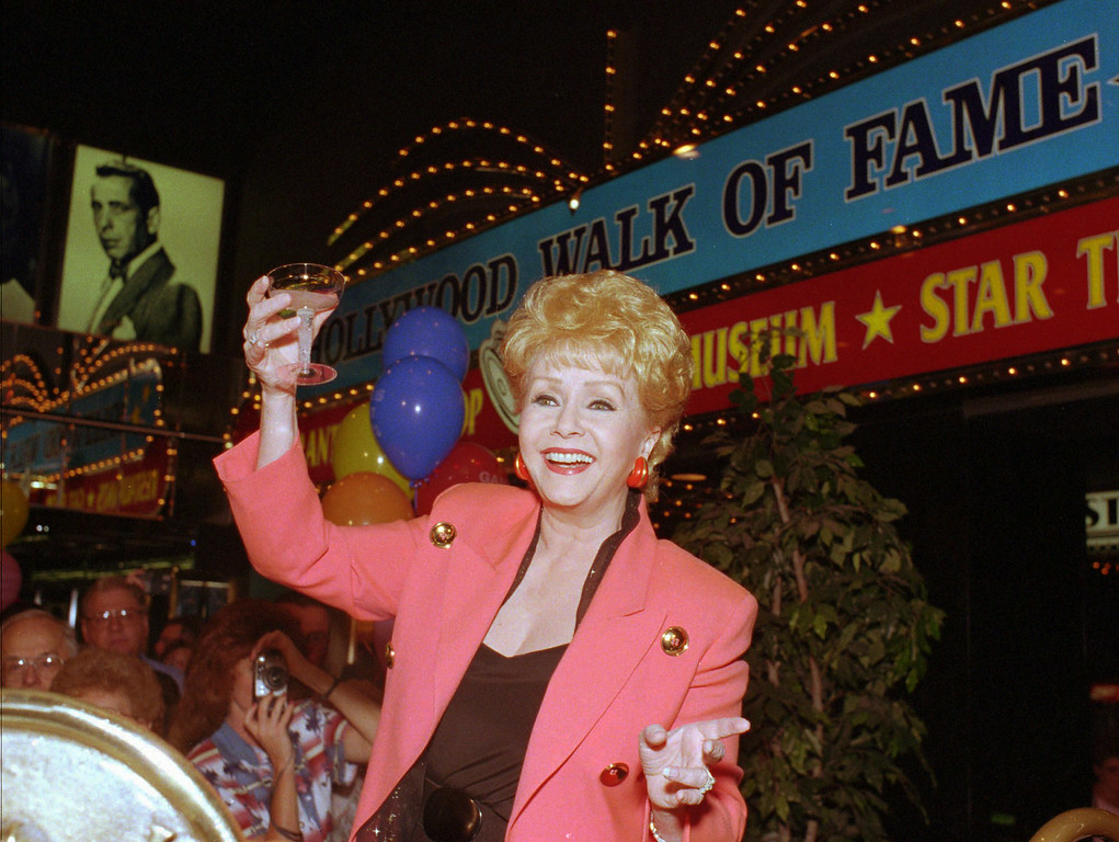 . Entertainer Debbie Reynolds reacts during an event inside the Debbie Reynolds Hotel & Casino in Las Vegas, Oct. 1, 1997.  (AP Photo/Lennox McLendon)