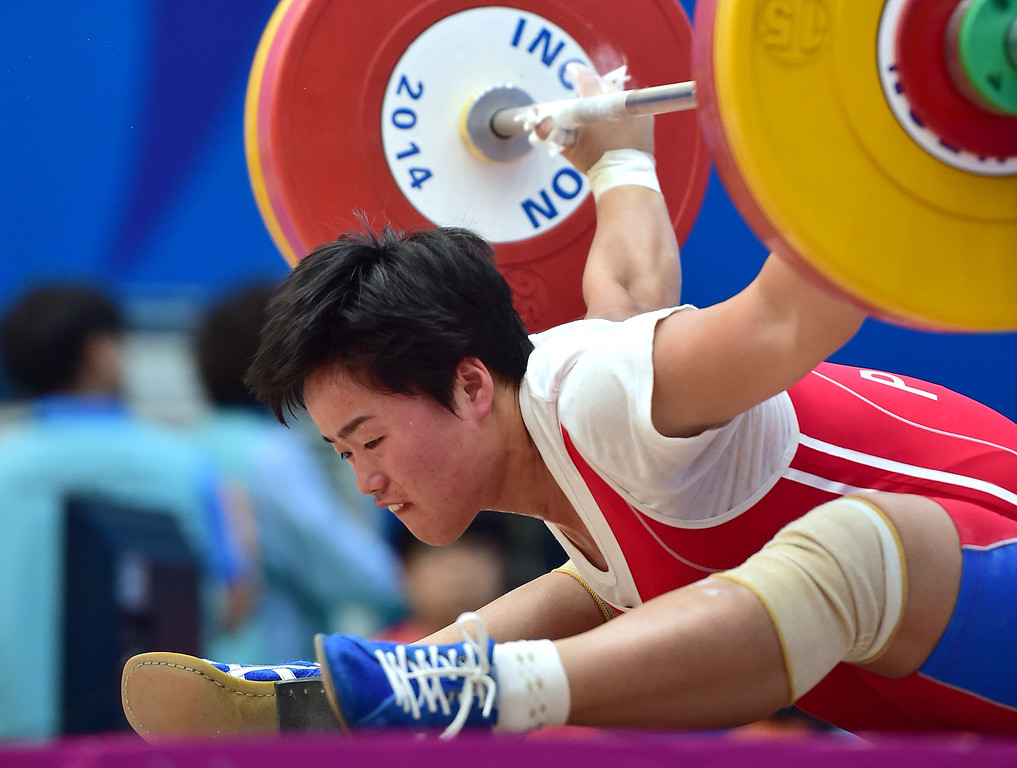 . North Korea\'s Jo Pok-Hyang falls as she misses a lift in the snatch of the women\'s 63kg weightlifting event during the 2014 Asian Games at the Moonlight Festival Garden in Incheon on September 23, 2014. JUNG YEON-JE/AFP/Getty Images