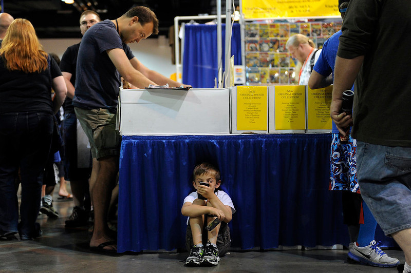 . Tate Reeder-Holman, 6, plays a game of Tetris on a cell phone as his dad, Dave Reeder, browses through a box of comic books during Denver Comic Con at the Colorado Convention Center on June 2, 2013 in Denver, Colorado. (Photo by Seth McConnell/The Denver Post)