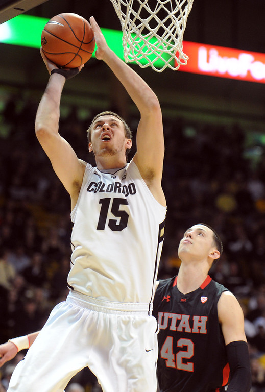 . Shane Harris-Tunks of CU scores past Jason Washburn of Utah during the first half of the February 21st, 2013 game in Boulder. For more photos of the game, go to www.dailycamera.com. Cliff Grassmick / February 21, 2013
