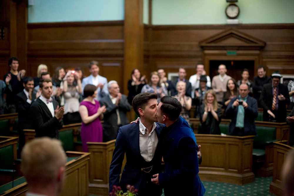 . Sean Adl-Tabatabai, left, and Sinclair Treadway kiss each other as they are announced officially married during a wedding ceremony in the Council Chamber at Camden Town Hall in London, minutes into Saturday, March 29, 2014. Gay couples in Britain waited decades for the right to get married. When the opportunity came, some had just days to plan the biggest moment of their lives. Adl-Tabatabai, a 32-year-old TV producer from London, and Treadway, a 20-year-old student originally from Los Angeles, registered their intent to marry on March 13, the first day gay couples could sign up for wedding ceremonies under Britain\'s new law. Eager to be part of history, the two men picked the earliest possible moment - just after midnight Friday, when the act legalizing same-sex marriage takes effect. (AP Photo/Matt Dunham)