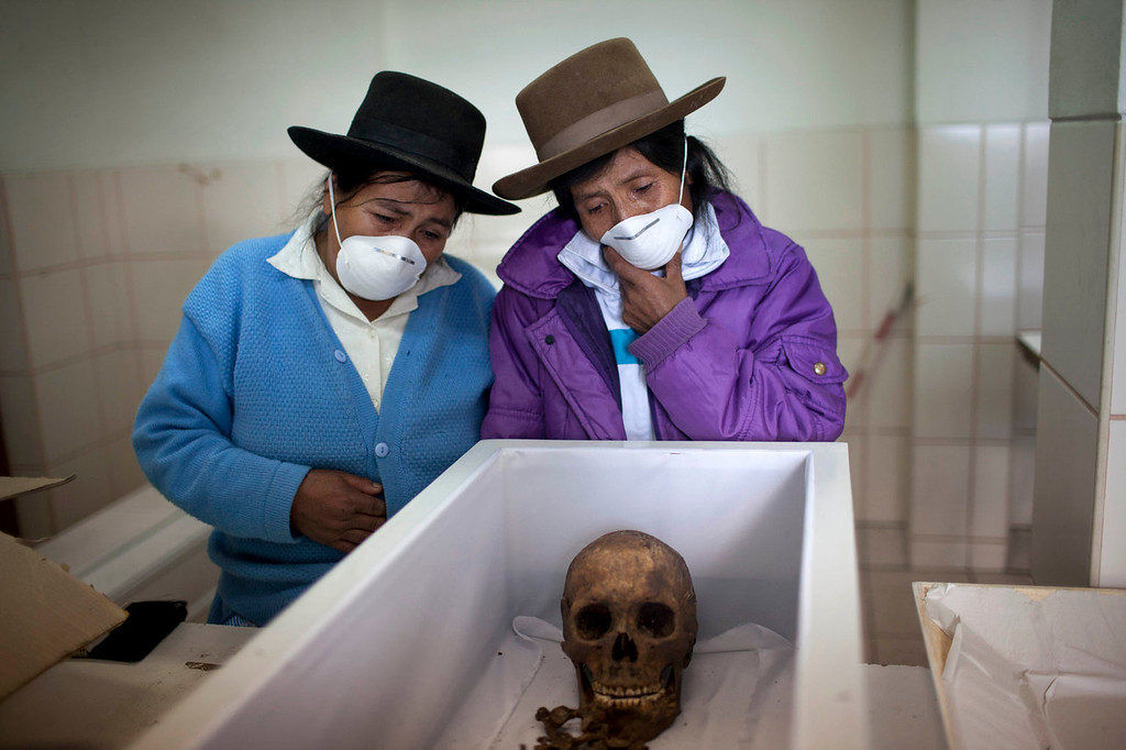 . Aquilina Cardenas, right, and her sister Luciana, look into the coffin containing the remains of their father in a forensic laboratory, in Ayacucho, Peru. Their father is one of the Chaca residents tortured and killed on Jan. 8,1988 by Shining Path militants in retaliation for forming a self-defense committee. The remains of the victims were exhumed in 2012 from a mass grave and released to family members on June 13, 2013. A mass burial was held in Chaca two days later.   (AP Photo/Rodrigo Abd)