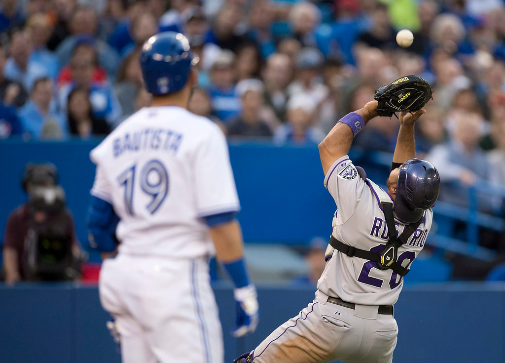 . Toronto Blue Jays\' Jose Bautista looks on as Colorado Rockies catcher Wilin Rosario makes the out on his pop up foul ball during fifth inning of an inter-league baseball game in Toronto on Tuesday June 18, 2013.   (AP Photo/The Canadian Press, Frank Gunn)