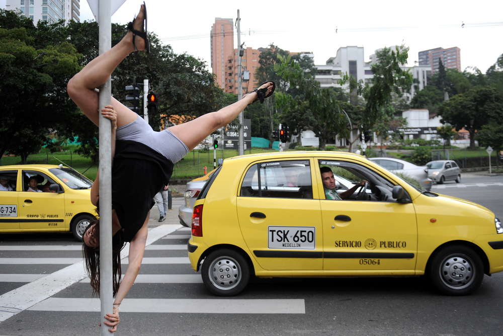 Description of . A woman performs her pole dancing routine at the streets in Medellin, Antioquia department, Colombia, on May 21, 2011.  AFP PHOTO/Raul ARBOLEDA