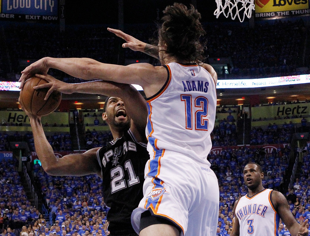 . San Antonio Spurs center Tim Duncan (21) is fouled by Oklahoma City Thunder center Steven Adams (12) as he shoots in the second quarter of Game 6 of a second-round NBA basketball playoff series in Oklahoma City, Thursday, May 12, 2016. (AP Photo/Alonzo Adams)