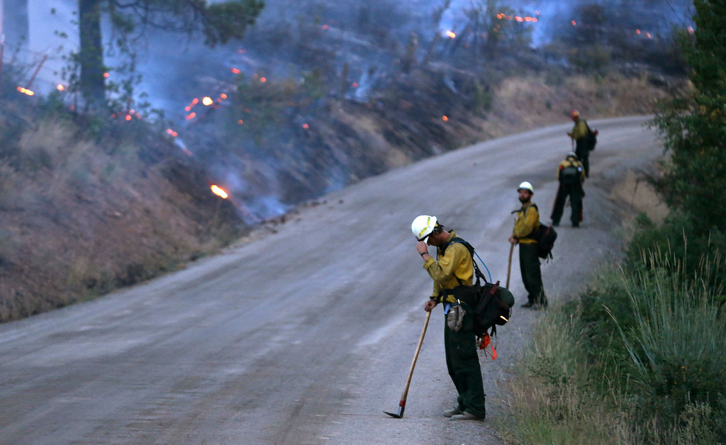 . A line of firefighters stands guard at dusk as they allow fire to burn to the road but keep an eye out to prevent embers from crossing Friday, July 18, 2014, in Winthrop, Wash. A fire racing through rural north-central Washington destroyed about 100 homes, leaving behind smoldering rubble, solitary brick chimneys and burned-out automobiles as it blackened hundreds of square miles. Friday\'s dawn revealed dramatic devastation, with the Okanagan County town of Pateros, home to 650 people, hit especially hard. (AP Photo/Elaine Thompson)