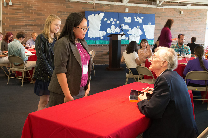 """Christina Chu (2014 Scholar)  with John Mather, as he signs copies of his book """"The Very First Light"""" -- An award luncheon, """"Dr. John Mather Nobel Scholars Program Award"""", as part of the National Space Grant Foundation. College Park Aviation Museum, College Park, MD, August 2, 2019."""