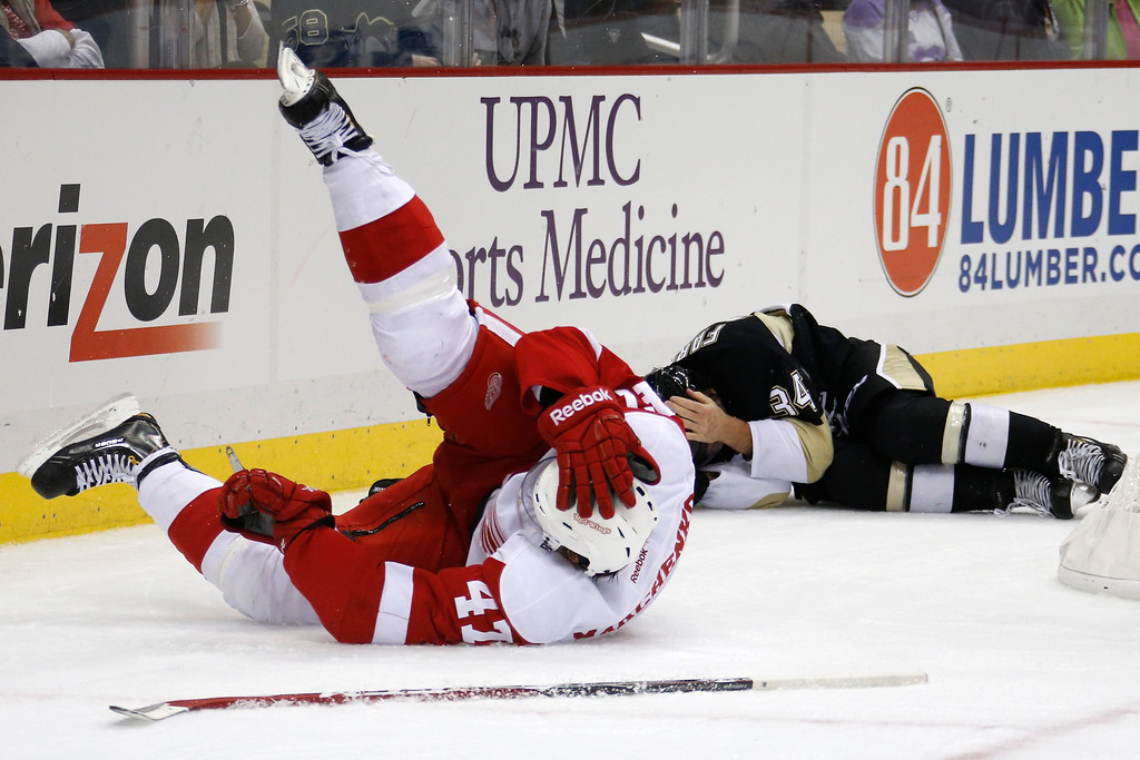 . Detroit Red Wings\' Alexei Marchenko, left, and Pittsburgh Penguins\' Bobby Farnham, rear, lie on the ice after slamming into the boards together during the second  period of a NHL pre-season hockey game in Pittsburgh Monday, Sept. 22, 2014. Both players remained in the game. (AP Photo/Gene J. Puskar)