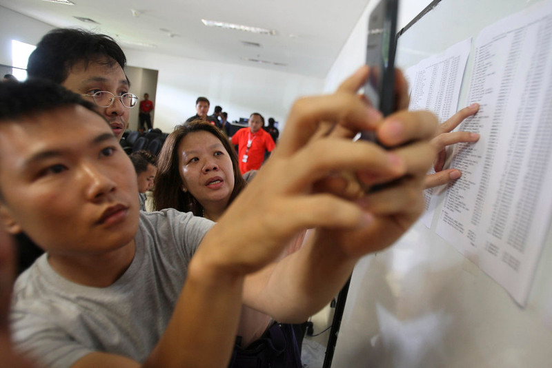. Relatives of the passengers onboard AirAsia flight QZ8501, check the plane\'s manifest at a crisis center set up by local authority at Juanda International Airport in Surabaya, East Java, Indonesia, Sunday, Dec. 28, 2014. The AirAsia plane with over 160 people onboard, lost contact with ground control on Sunday while flying over the Java Sea after taking off from the provincial city in Indonesia for Singapore. (AP Photo/Trisnadi)