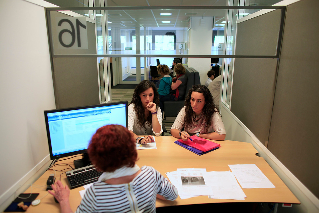 . Spanish nurses Maria Jose Marin (L), 23, and her twin sister Maria Teresa speak to an advisor at an immigration office in The Hague, June 5, 2013. After months of studying Dutch, a group of young Spanish nurses moved to the Netherlands to take up work, fleeing a dismal job market at home. Spain\'s population dropped last year for the first time on record as young professionals and immigrants who moved here during a construction boom head for greener pastures. Spain\'s jobless rate is 27 percent, and more than half of young workers are unemployed. For Spanish nurses, the Netherlands\' nursing deficit is a boon. Picture taken June 5, 2013. REUTERS/Marcelo del Pozo