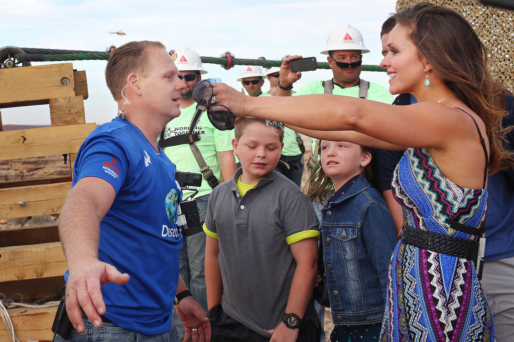 . Aerialist Nik Wallenda, left, is welcomed by his wife, Erendira, after walking a 2-inch-thick steel cable that took him a quarter mile over the Little Colorado River Gorge in northeastern Arizona on Sunday, June 23, 2013. The daredevil successfully traversed the tightrope strung 1,500 feet above the chasm on the Navajo Nation near the Grand Canyon in just more than 22 minutes, pausing and crouching twice as winds whipped around him and the cable swayed. (AP Photos/Discovery Channel, Tiffany Brown)