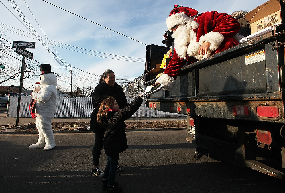 Description of . Mike 'Loco' Hoffman, aka Santa Claus, passes out free gifts from the back of a truck to Gloria Lullo and her granddaughter Jolee in the Midland Beach neighborhood which was heavily damaged by Superstorm Sandy on December 23, 2012 in the Staten Island borough of New York City. Staten Island was hit hard by Sandy and some homes and businesses remain without power.  (Photo by Mario Tama/Getty Images)