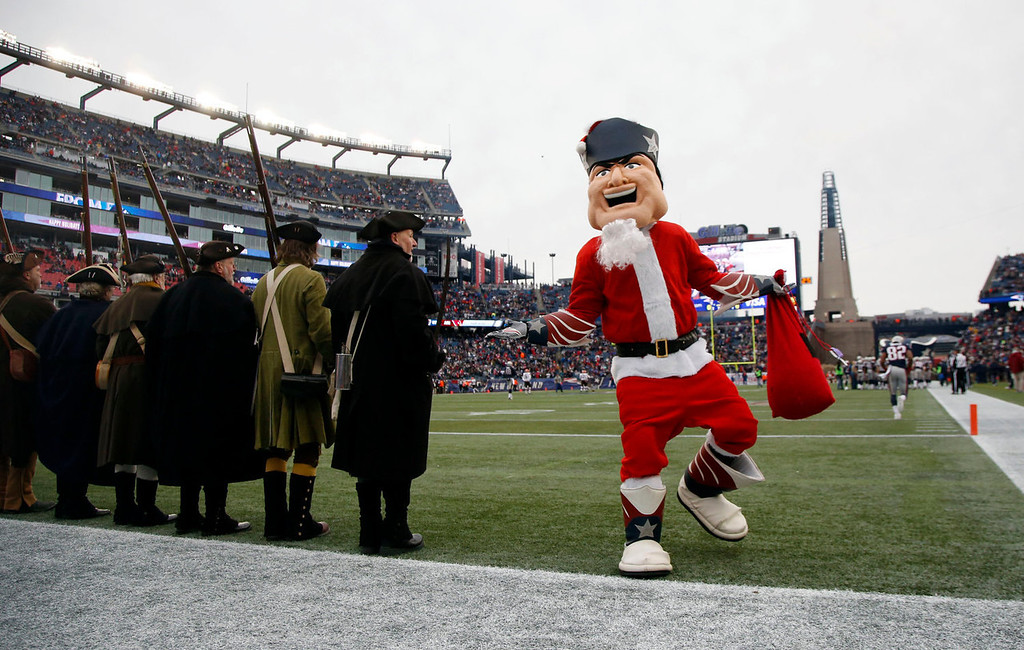 . The New England Patriots mascot runs past patriot soldier re-enactors before an NFL football game between the Patriots and the Cleveland Browns, Sunday, Dec. 8, 2013, in Foxborough, Mass. (AP Photo/Elise Amendola)