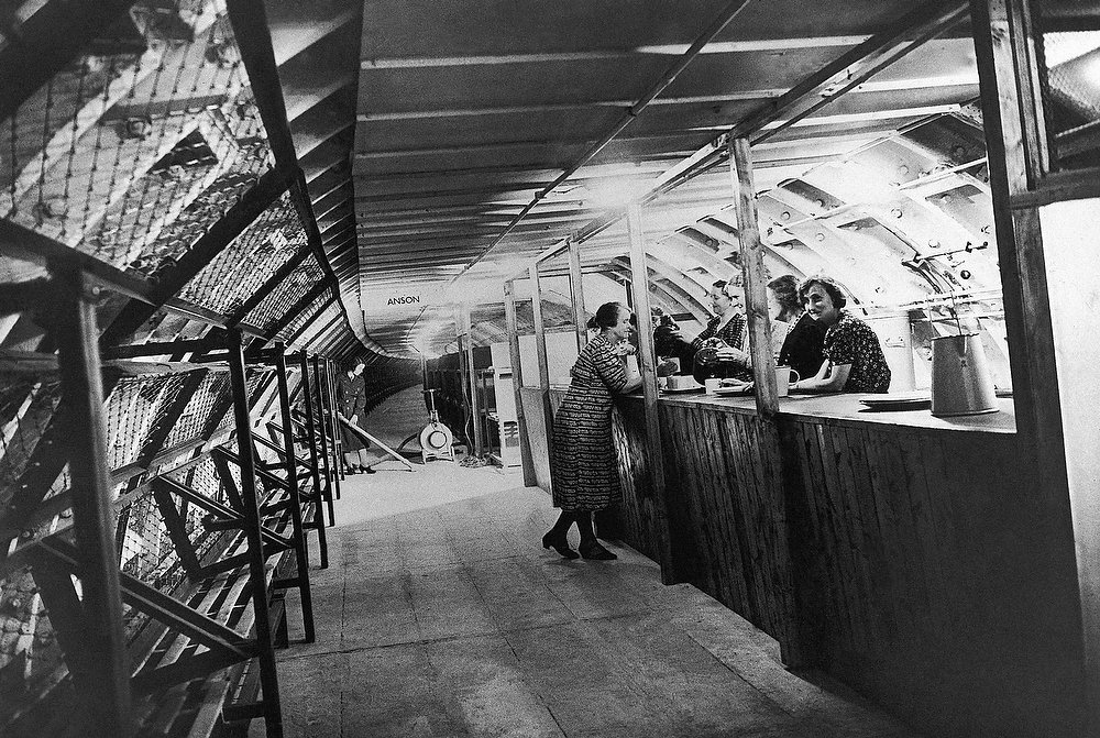 Description of . A canteen in one of London's new deep underground air raid shelters on Oct. 20, 1942. Note the line of bunks which are convertible into seats on the left wall. (AP Photo)