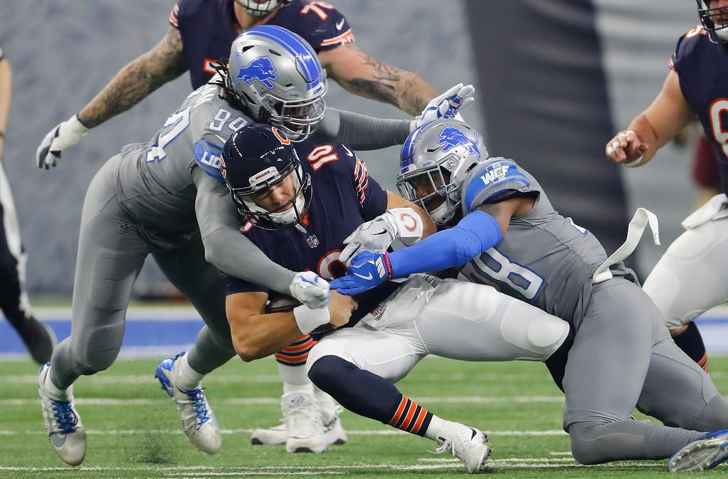 . Detroit Lions defensive end Ezekiel Ansah (94) and Detroit Lions cornerback Quandre Diggs (28) bring down Chicago Bears quarterback Mitchell Trubisky (10) during an NFL football game in Detroit, Saturday, Dec. 16, 2017. (AP Photo/Paul Sancya)