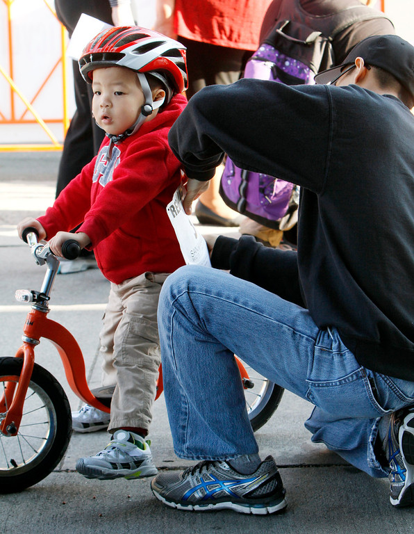. Brandon Gabot, 3, left, gets his bib pinned on by his father Mark prior to the start of the public race portion of the Redlands Bicycle Classic on Saturday, April 5, 2014 in Redlands, Ca. (Photo by Micah Escamilla for the Redlands Daily Facts)
