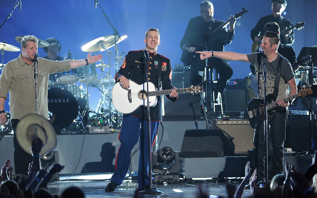 . Brandon Valentine, of the U.S. Marine Corps, center, and from left, Gary LeVox and Jay DeMarcus, of the musical group Rascal Flatts, perform at ACM Presents an All-Star Salute to the Troops on Monday, April 7, 2014, in Las Vegas. (Photo by Chris Pizzello/Invision/AP)