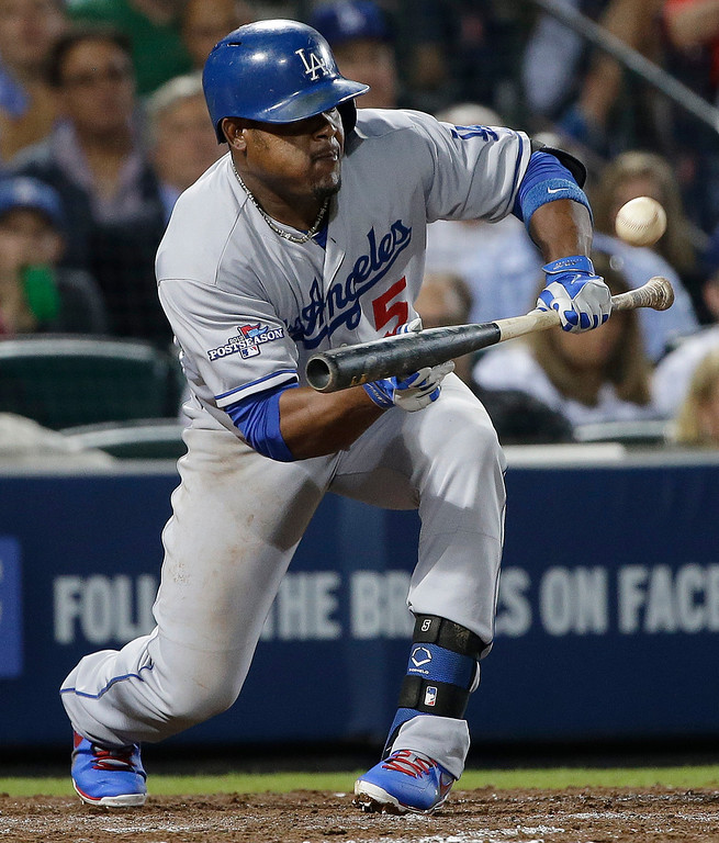 . Los Angeles Dodgers third baseman Juan Uribe (5) hits a sacrifice bunt in the fifth inning advancing Adrian Gonzalez to third base and  Yasiel Puigto second base against the Atlanta Braves during Game 1 of the National League Division Series, Thursday, Oct. 3, 2013, in Atlanta. (AP Photo/John Bazemore)
