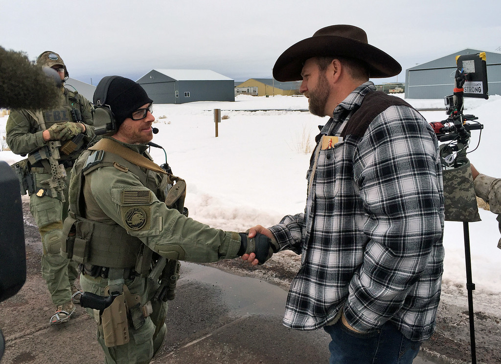 . Ammon Bundy, right, shakes hand with a federal agent guarding the gate at the Burns Municipal Airport in Oregon on Friday, Jan. 22, 2016. Bundy is the leader of an armed group occupying a national wildlife refuge to protest federal land policies. (AP Photo/Keith Ridler).