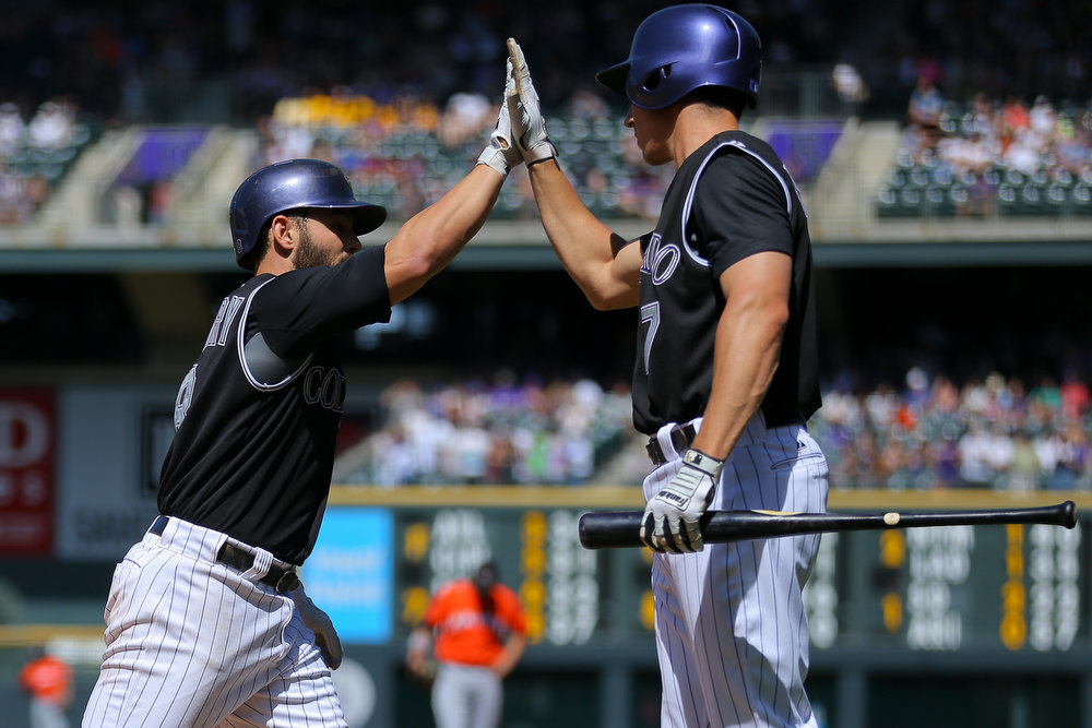 . Michael McKenry #8 of the Colorado Rockies is congratulated by Matt McBride #7 after his solo home run during the first inning against the Miami Marlins at Coors Field on August 24, 2014 in Denver, Colorado.  (Photo by Justin Edmonds/Getty Images)