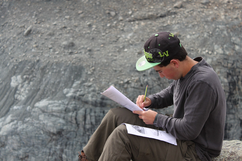 Andrew working on his geology lab with the glacier and moraine below