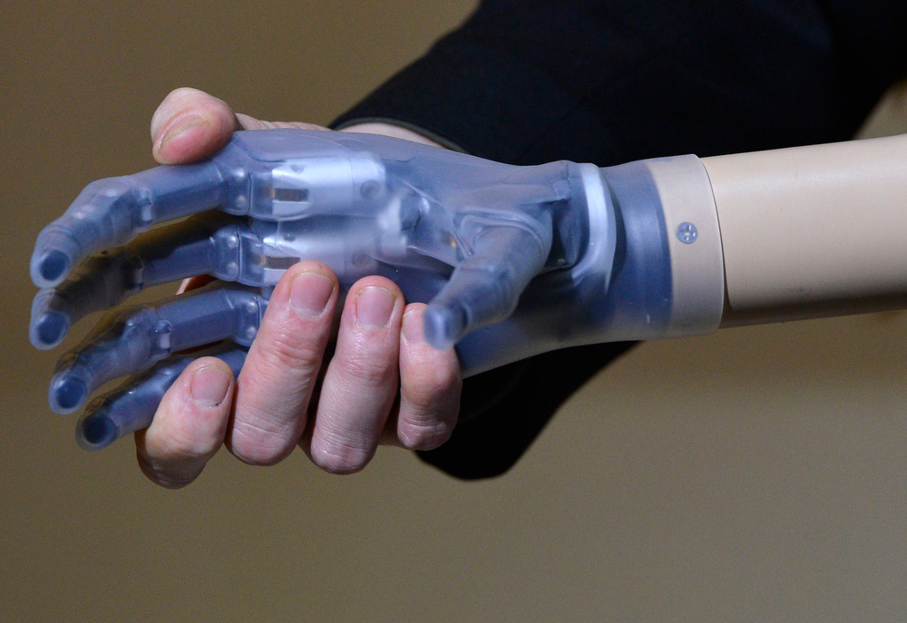 . A designer hold the hand of \'Rex\', a two metre tall artificial human, at the Science Museum in central London February 5, 2013. The British roboticist designers claim it is the world\'s first complete bionic man, featuring artificial organs as well as fully functioning limbs. It will be on public display until March 11. REUTERS/Toby Melville