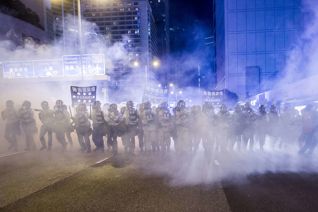 . Police officers stand in a cloud of tear gas during a demonstration in Hong Kong on September 28, 2014.  AFP PHOTO / XAUME  OLLEROS/AFP/Getty Images