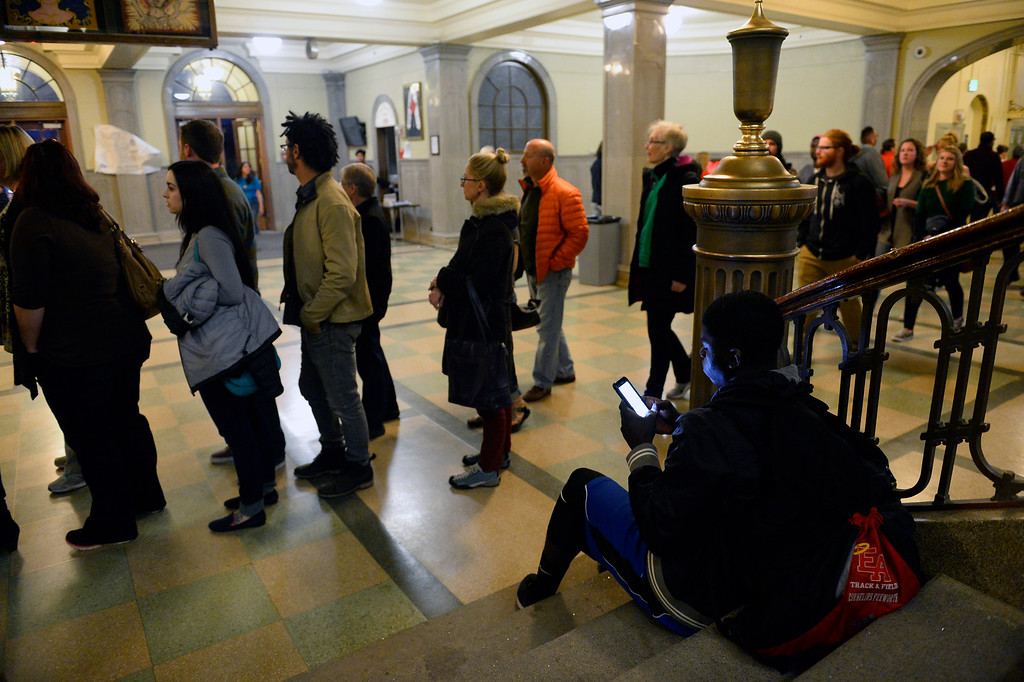. East High school student Cornelius Foxworth, right,  waits on the stairs as thousands of people who turned out for the democratic caucus, wait in line to register at East High School  in Denver, Colorado on March 1, 2016. (Photo by Helen H. Richardson/The Denver Post)
