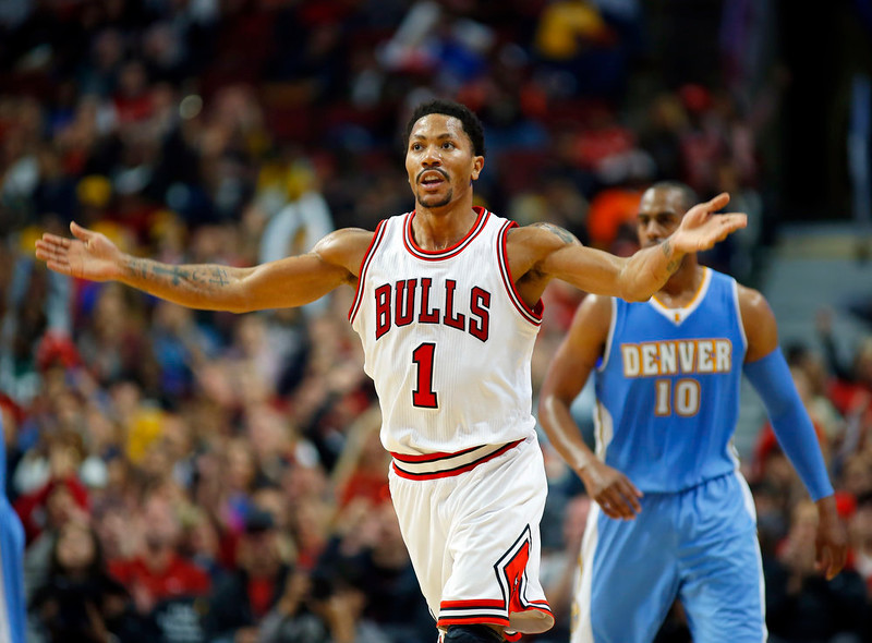 . Chicago Bulls guard Derrick Rose (1) reacts to the crowd after making a three point basket against the Denver Nuggets during the first half of a pre-season NBA basketball game in Chicago, on Monday Oct. 13, 2014. (AP Photo/Jeff Haynes)